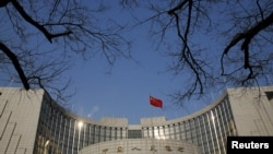 A Chinese national flag flies at the headquarters of the People's Bank of China, the country's central bank, in Beijing, China, Jan. 19, 2016.