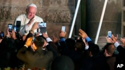 Faithful take photos with their mobile phones as Pope Francis departs from San Francisco Church aboard the Popemobile, in Quito, Ecuador, July 7, 2015.