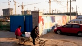 Workers ride a tricycle outside a construction site of a residential real estate project in Beijing, China, January 13, 2013.