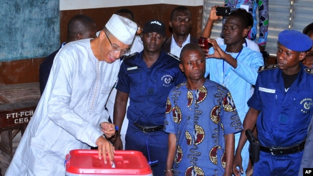 Presidential candidate, Benin prime minister Lionel Zinsou, left, casts his ballot during the election in Cotonou, March  6, 2016.