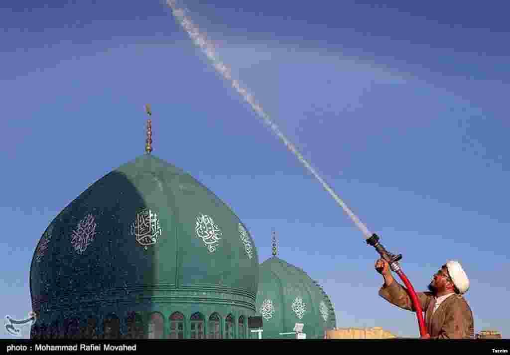 این آقا با این شلنگ مشغول شست و شوی گنبد و تعویض پرچم مسجد جمکران است. عکس: محمد رفیعی موحد