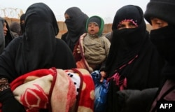 FILE - Syrian refugee women holding children are seen at Rukban camp, located in a no-man's-land on the border between Syria and Jordan, March 1, 2017.