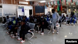 FILE - Guinean migrants wait at the airport before being deported to Guinea, in Misrata, Libya, Dec. 27, 2017.