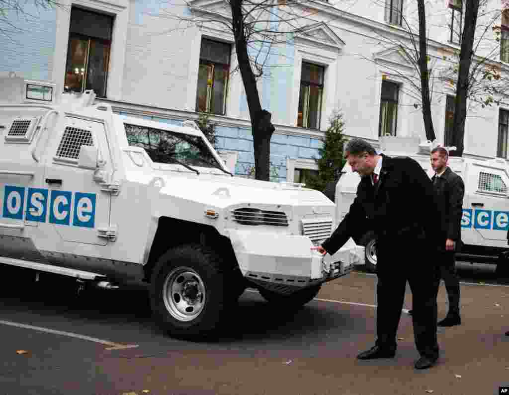 Ukrainian President Petro Poroshenko inspects an armored vehicle at the official handover of 10 armored vehicles to a monitoring team from Organization for Security and Cooperation in Europe on Thursday Nov. 13, 2014.