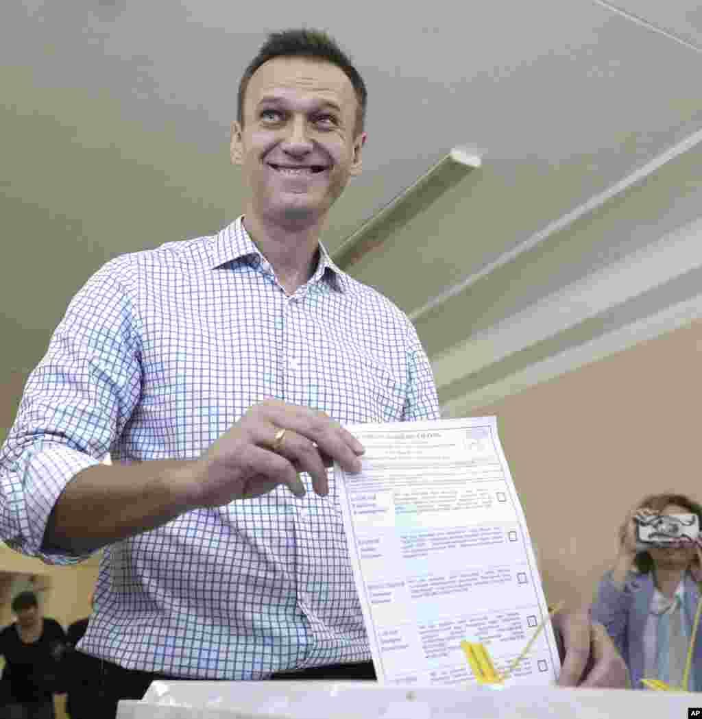 آلکسی ناوالنی حقوقدان و از چهره های مخالف پوتین است که به تازگی از زندان آزاد شد. او در انتخابات امروز شورای شهر مسکو برگه رای خود را به عکاسان نشان می دهد.