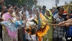 Activists from India's main opposition Bharatiya Janata Party (BJP) burn an effigy representing chief of ruling Congress Party Sonia Gandhi during a protest in Noida, Uttar Pradesh on June 6, 2011.