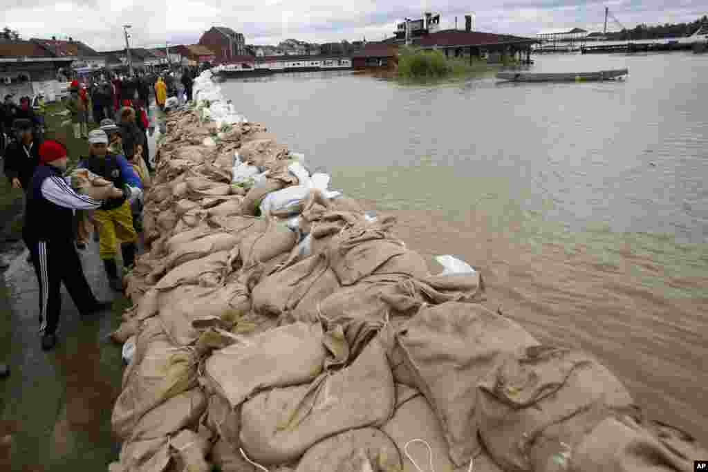 People build a dam made up of sandbags by the bank of the Sava river in Sremska Mitrovica, Serbia, May 17, 2014.