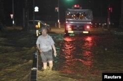 A man walks through a flooded street in Asakura, Fukuoka prefecture, Japan, in this photo taken by Kyodo, July 5, 2017.