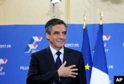 FILE - Francois Fillon puts his hand on his heart after delivering a speech following the conservative presidential primary, in Paris, France, Nov. 27, 2016.