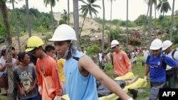 Nhân viên cứu hộ khiêng xác một nạn nhân ra khỏi khu vực bị đất chuồi sau vụ động đất ở La Libertad, miền Trung Philippines, ngày 7/2/2012