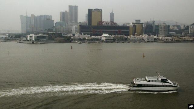 FILE - A ferry sails across the Casino Sands' Macau, Dec.19, 2009.