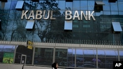 An Afghan girl walks past by Kabul Bank's main office in Kabul, Afghanistan, March 27, 2011.