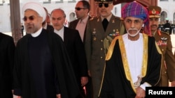 FILE - Oman's Sultan Qaboos bin Said (R) walks with Iran's President Hassan Rouhani upon Rouhani's arrival in Muscat, Oman, March 12, 2014.