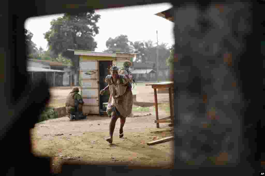 A woman runs for cover as heavy gunfire erupts in the Miskin district of Bangui, Central African Republic. In what a French soldier on the scene described as the heaviest exchange of fire he'd seen since early December 2013, Muslim militias engaged Burundi troops who returned fire.