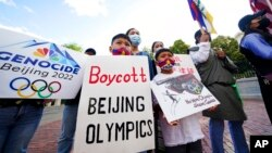 FILE - Children hold signs during a demonstration by a coalition representing Tibetans, Uyghurs, Southern Mongolians, Hong Kongers, Taiwanese and Chinese rights activists in Boston, June 23, 2021.