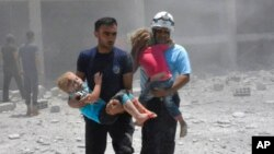 Syrian Civil Defense group known as the White Helmets carrying children after airstrikes hit a school housing a number of displaced people, in the western part of the southern Daraa province of Syria. (File)