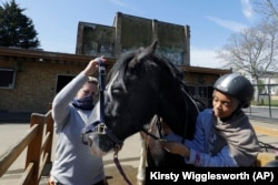 Tasneem Aly, right, and General manager Naomi Howgate take the harness off Bailey after a riding lesson at Ebony Horse Club in Brixton, south London, April 18, 2021