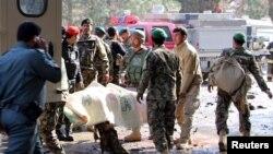 Афганські солдати несуть жертву атаки до карети швидкої допомоги