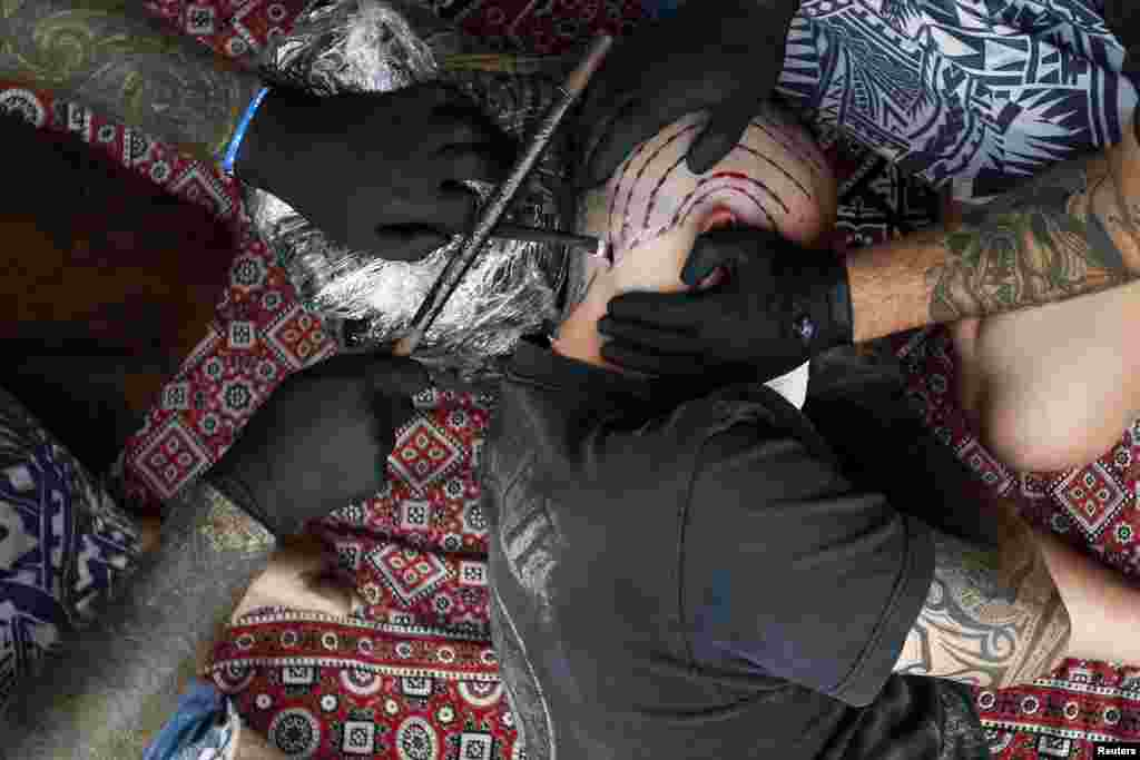 A man is tattooed by tattoo artist Brent McCown (L) during the ninth London Tattoo Convention.