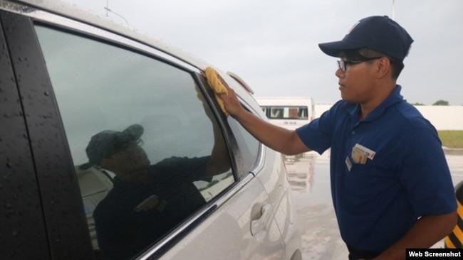 Một nhân viên của trạm xăng lau kính ôtô cho một khách hàng.