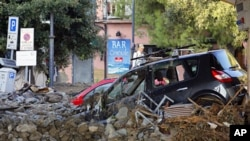 Broken cars are blocked in mud and debris in a street of Monterosso, one of the five villages that make up the Five Lands after overnight floods in the Spezia region, October 26, 2011