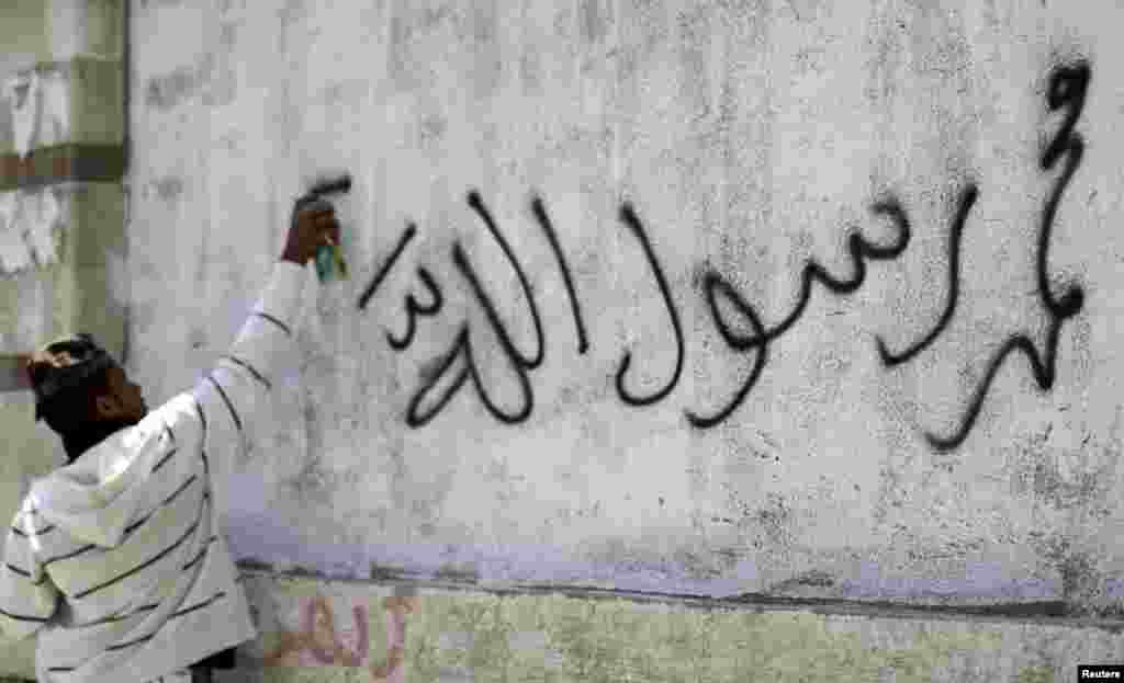 A protester sprays graffiti on a wall during a protest march to the U.S. embassy in Sanaa September 13, 2012.