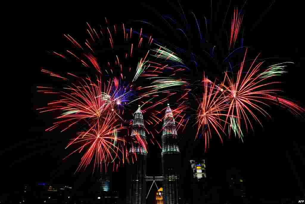 Fireworks explode near Malaysia's landmark Petronas Twin Towers in Kuala Lumpur during the New Year 2014 celebrations.