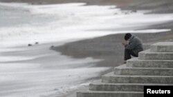 지난 3월 일본 후쿠시마 이와키의 바다에서 여성이 2011년 쓰나미로 숨진 희생자들을 추모하고 있다. (자료사진)