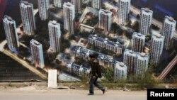 Hình minh họa - Một người đàn ông đi ngang qua một bức tường ở công trường xây dựng khu dân cư mới ở Thiên Tân, Trung Quốc.