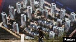 有人走过天津滨海新区一处新居民楼群的墙壁(2015年10月18日)