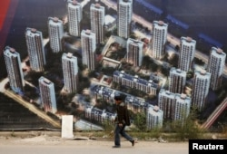 有人走过天津滨海新区一处新居民楼群的墙壁,墙上贴着的画布上高楼林立(2015年10月18日)
