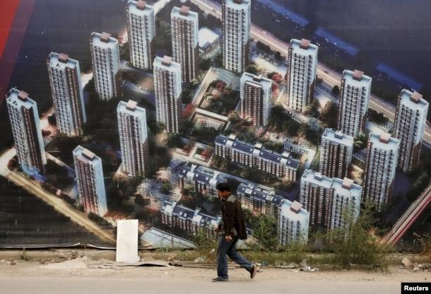 有人走过天津滨海新区一处新居民楼群的墙壁,墙上有楼群的图片(2015年10月18日)