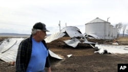 This photo taken March 12, 2020, near Rock Port, Missouri, shows tenant farmer Phil Graves examining grain storage bins that were destroyed in a 2019 flood.