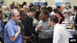Những người đi xin việc đang nói chuyện với các nhà tuyển dụng tại một hội chợ việc làm ở Arlington, bang Virginia.
