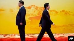 亚太经合组织峰会的欢迎仪式上,日本首相安倍(右)从中国国家主席习近平身边走过(资料照)
