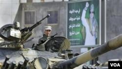 Seorang tentara Libya yang setia kepada Moammar Gadhafi siaga dengan mengendarai tank di kota Qasr Banashir, tenggara ibukota Tripoli (1/3).