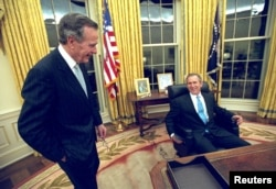 FILE - U.S. President George W. Bush sits at his desk in the Oval Office for the first time on Inaugural Day, in this January 20, 2001 file photo, as his father, former President George H.W. Bush looks on.