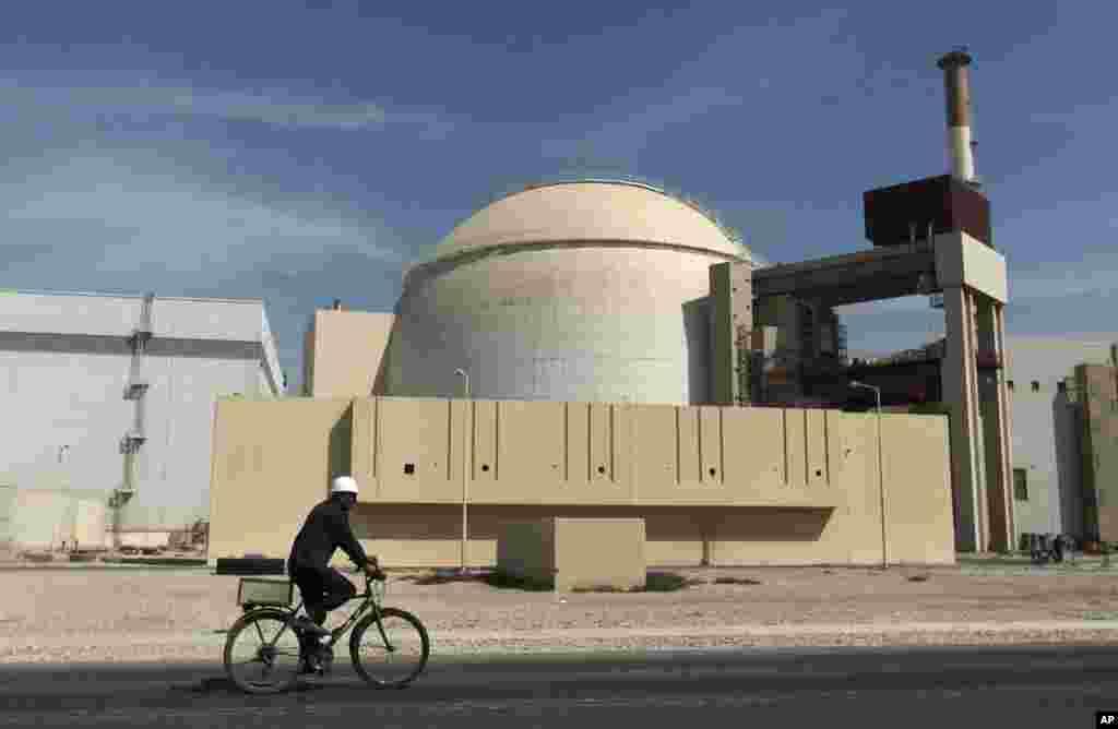 Foto bertanggal 26 Oktober 2010 yang memperlihatkan seorang pekerja bersepeda melewati bangunan reaktor pembangkit listrik tenaga nuklir di luar kota Bushehr, selatan Iran. (AP/Mehr News Agency, Majid Asgaripour)