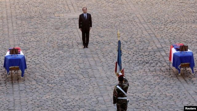French President Francois Hollande pays his respects in front of the two flag-draped coffins bearing the French soldiers who died  last week in the Central African Republic, during a ceremony at the Invalides, in Paris, Dec. 16, 2013.