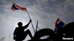 Seorang demonstran anti-pemerintah mengibarkan bendera di atas barikade di dekat kantor pemerintah di Bangkok (18/2). (Reuters/Damir Sagolj)