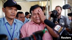 FILE - Soum Rithy (C), who lost his father and three siblings during Khmer Rouge regime, is escorted after the verdict was delivered in the trial of former Khmer Rouge head of state Khieu Samphan and former Khmer Rouge leader Nuon Chea, at the Cambodia courthouse on the outskirts Phnom Penh, Aug. 7, 2014.