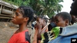 Un groupe de femmes regardent les équipes de secours qui ramassent des corps après un accident de train à Kananga, Kasaï occidental, 4 août 2007.