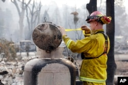 Fire Capt. Roger Lutz tags a leaking gas tank in the remains of a home destroyed in a wildfire several days earlier, Sept. 15, 2015, in Middletown, Calif.