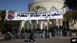Polisi anti huru-hara Mesir menjaga ketat istana presiden di Kairo (8/12). Di depan istana Presiden tersebut terbentang spanduk bergambar Presiden Morsi yang bertuliskan keinginan warga Mesir agar Presiden mundur dari jabatan.