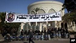 一名埃及人行經防暴警察保護下的總統府前.可看到上方懸掛出要總統下台的橫幅