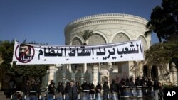 ຊາວອີຈິບຄົນນຶ່ງຍ່າງກາຍຕຳຫຼວດປາບຈະລາຈົນ ທີ່ຍາມປະຕູທາງເຂົ້າທຳນຽບປະທານາທິບໍດີ ຢູ່ລຸ້ມປ້າຍຄຳຂວັນທີ່ຂຽນເປັນພາສາອາຣັບວ່າ ປະຊາຊົນຕ້ອງການທຳລາຍອຳນາດ ການປົກຄອງນີ້ ແລະຮູບປະທານາທິບໍດີ Mohammed Morsi ທີ່ຖືກຂີດໜ້າ (8 ທັນວາ 2012)