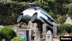Një makinë shfaqet e ndalur mbi një varrezë pas tërheqjes së ujërave në Dernau, Gjermani