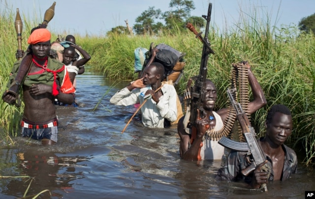 FILE - Rebel soldiers are seen protecting civilians from the Nuer ethnic group as they walk through flooded areas to reach a makeshift U.N. camp for the displaced in the town of Bentiu, South Sudan, Sept. 20, 2014. After two years of civil war, rebel leader Machar and South Sudan President Salva Kiir signed a peace deal in August 2015.