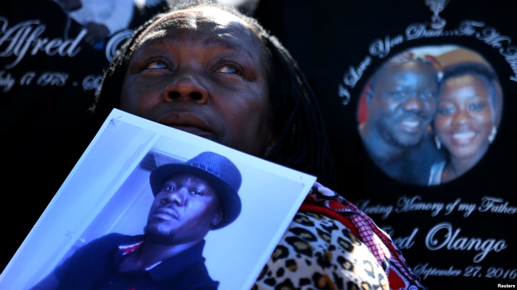 FILE - A woman holds a picture of Alfred Olango as she listens to speeches during an Oct. 1, 2016, rally and march to protest the fatal police shooting of the Ugandan immigrant in El Cajon, California, four days earlier.