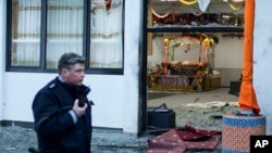 FILE - In this April 16, 2016, photo, a police officer walks in front of a Sikh temple after an explosion near it injured three people and damaged the structure, in the western German city of Essen.